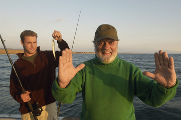 Father gesturing fish size on boat, portrait