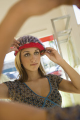 Young woman trying on hat in shop