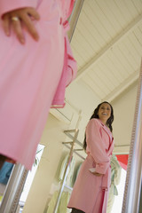 Young woman trying on pink trench coat in shop
