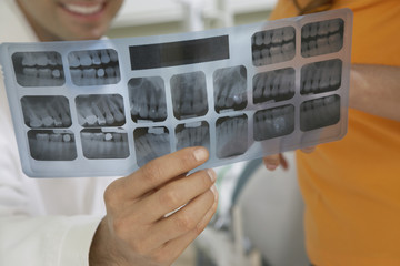 Dentist and patient examining X-rays, close-up