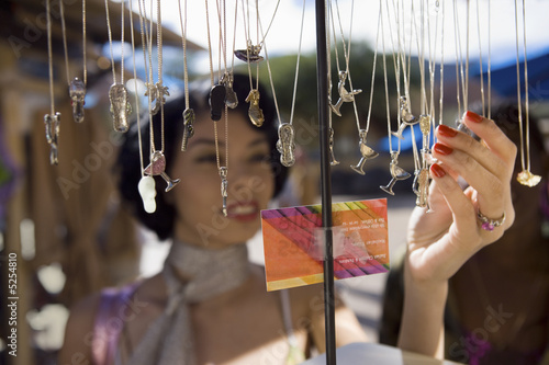 Young woman shopping for necklaces