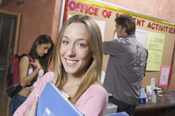 Female student in college office, clutching folder