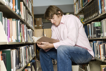 Male college student sitting, reading in library
