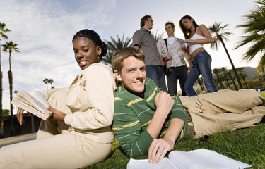 College students on campus lawn, studying