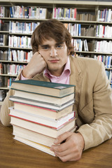 Male college student in library with  stack of books