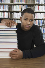 Male student with a stack of books in library