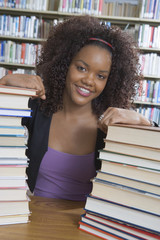 Female  student in college library, with stacks of books