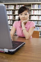 Bored female student working on laptop in library