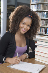 Enthusiastic female student studying at library