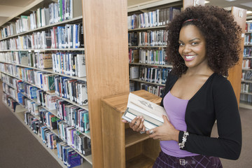 Female student choosing books in library