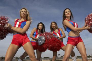 Cheerleaders doing routine with pom poms on football field