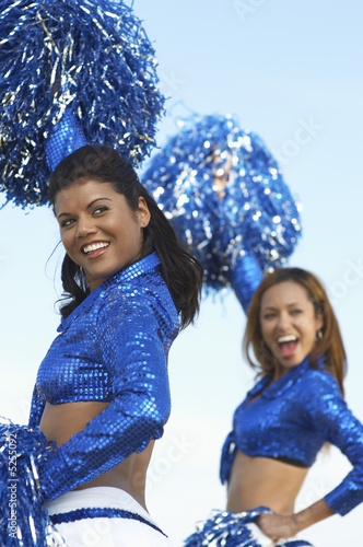 Cheerleaders with pom poms raised looking over shoulder