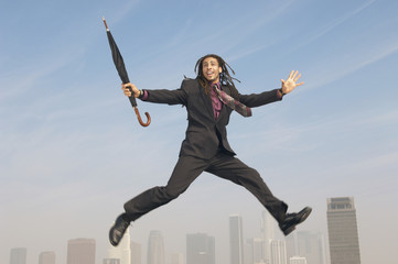 Business man jumping with closed umbrella mid-air above city
