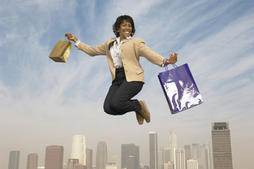 Woman jumping with shopping bags mid-air above city