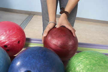 Young woman selecting bowling ball, mid section