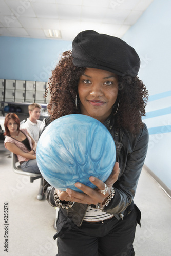 Young woman at bowling alley holding ball, portrait