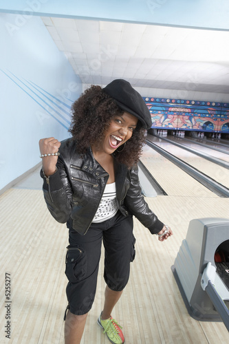 Young woman at bowling alley celebrating, portrait