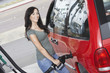 Young woman filling car with gas at gas station, elevated view