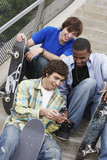 Three skateboarders sitting on stairs using cell phone