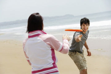 Young couple playing Frisbee on Beach