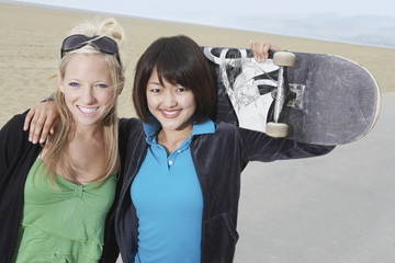 Two young female skateboarders on beach, portrait