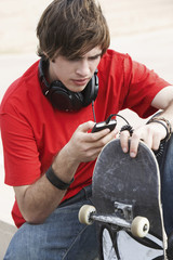 Young skateboarder using MP3 Player outside