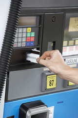 Person paying with credit card at gas pump, close up of hand