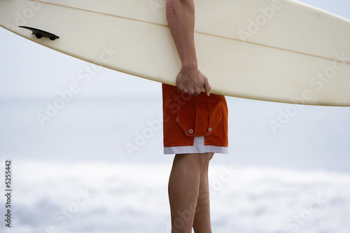 Man holding surfboard on beach, mid section