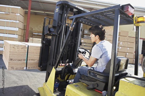 Man operating forklift outside, rear view