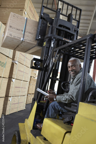 Man using forklift to lift box in warehouse