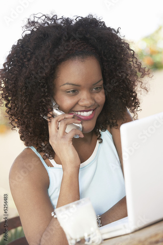 Woman using mobile phone while sitting in front of laptop, portrait