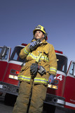 Fire fighter using two way radio in front of fire engine, low angle view