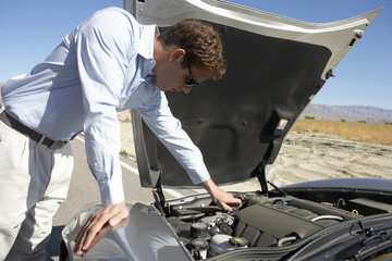 Man looking at engine of sports car by side of desert road