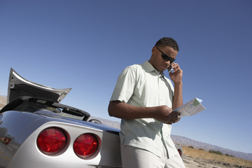 Man using cell phone and map by sports car at side of road