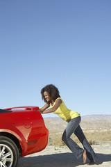 Women pushing broken down sports car on desert road
