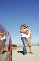 Couple with sports car taking photos by side of desert road