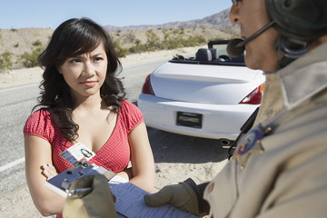 Police officer ticketing  young woman driver on desert highway