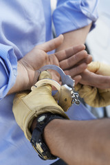 Police officer handcuffing man, close up on hands