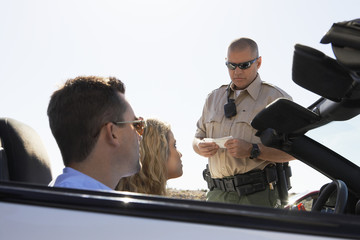 Police officer issuing ticket to couple in car