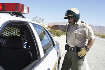 Police officer standing by police car on desert highway