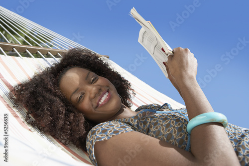 Woman reading in hammock, half length