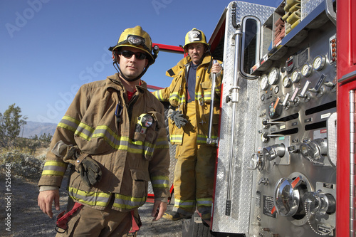Two fire fighters standing by fire engine