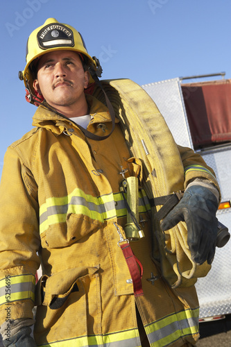 Fire fighter standing with hose on shoulder