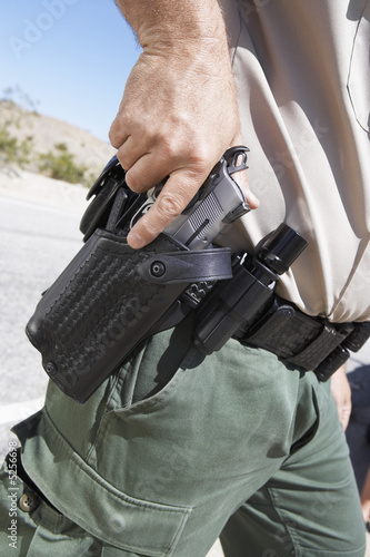 Police officer drawing  gun from holster, mid section, mid section
