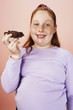Overweight girl 13-15 smiling, holding brownie, portrait, front view