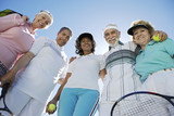 Seniors standing in half circle, holding rackets and balls, low angle view