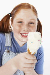 Overweight girl 13-15 smiling, cream on face, holding ice cream cone, portrait