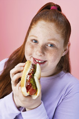 Overweight girl 13-15 Eating hot dog, portrait, close-up