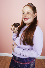 Overweight girl 13-15 smiling, holding brownie, hand on belly