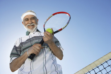 Smiling Man holding racket and ball, standing above net, low angle view